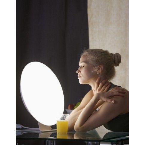 Lampa przeciwdepresyjna Rondo to elegancka, stylowa domowa lampa do świtłoterapi jasnym światłem. Posiada niski poziom jaskrawości, co czyni ją przyjazną dla oczu, co jest ważne dla osób szczególnie wrażliwych na jasne światło. Jej okrągła obudowa, kojarząca się z tarczą słoneczną, tworzy ciepłe odczucie słońca i lata. Urządzenie posiada regulator natężenia oświetlenia. Dostępna na www.OrtoModa.pl