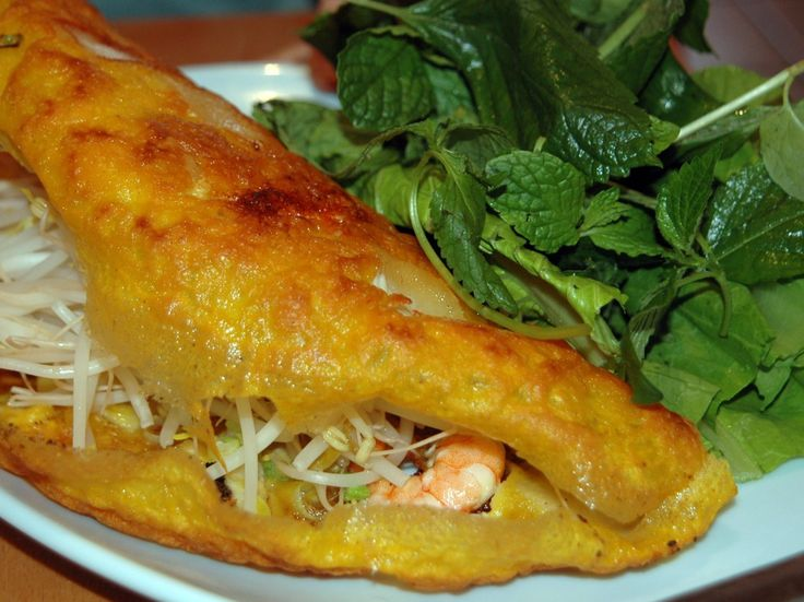 """Banh xeo (""""bahn SAY-oh"""") is a popular street snack in Vietnam, especially the south. The name means """"sound crepe,"""" and it indicates the sound the batter makes when it hits the hot skillet. The shrimp-studded crepe is rolled up in a leaf of lettuce and dipped in a flavorful lime-scented sauce before it gets popped in your mouth. Makes about 4 to 6 filled crepes Ingredients Crepe Batter"""