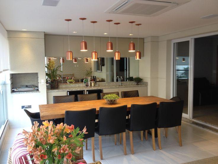 Projeto MT  Varanda Gourmet TATIANA BARONI com luminárias pendentes em cobre, mesa rústica em madeira com toque moderno, armários laqueados feitos sob medida para abrigar um frigobar e uma adega, as cadeiras pretas e o espelho trazem sofisticação ao ambiente