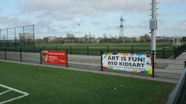 Reclameborden langs de kant van het voetbalveld. En natuurlijk hebben we zelf ook een bord.