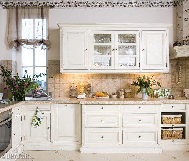 <p><strong>Aranżacja kuchni</strong> z rozbudowaną zabudową kuchenną i wygodnym aneksem jadalnianym w <strong>stylu prowansalskim</strong> jest ciepła i przytulna. Kuchnia jest stylowa, a drewniane białe szafki, płytki ceramiczne i dekoracyjna tapeta z motywem czarnych oliwek przywołują klimat Prowansji.</p>
