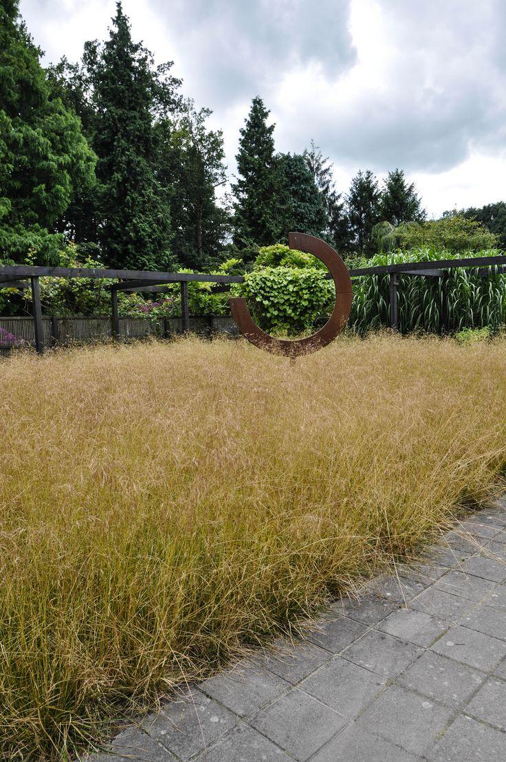 Maak een tuin persoonlijk. Bijvoorbeeld door kunst erin te verwerken. Deze siergrassen verkleuren trouwens fantastisch gedurende het jaar. Mien Ruys,