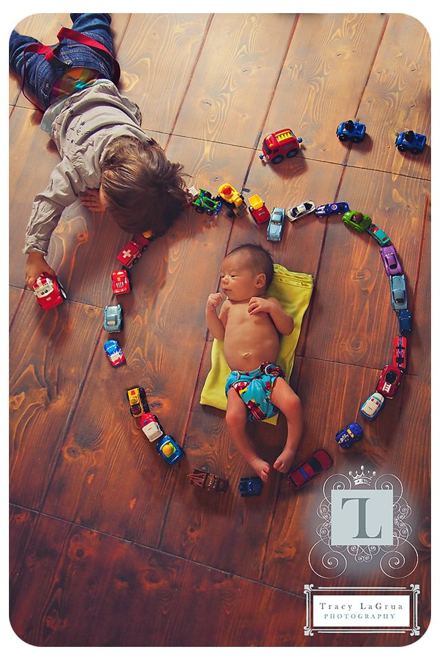 newborn baby playing with older sibling