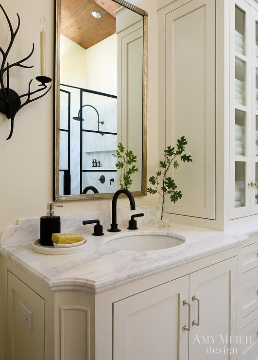 Ivory bathroom features an ivory wall lined with ivory washstand topped with white marble fitted with an oil rubbed bronze gooseneck faucet under a metal framed mirror.