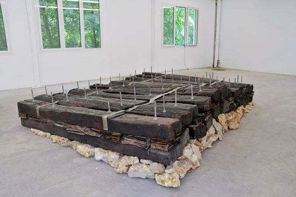 Chen Zhen, Le Chemin / Le Radeau de lécriture, 1991, railway sleepers, metal, stone, newspapers, cm 60 x 300 x 250.