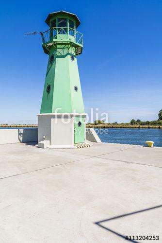 """Pobierz zdjęcie royalty free  """"Green lighthouse on the waterfront."""" autorstwa gubernat w najniższej cenie na Fotolia.com. Przeglądaj naszą bazę tanich obrazów online i odnajdź doskonałe zdjęcie stockowe do Twoich projektów reklamowych!"""