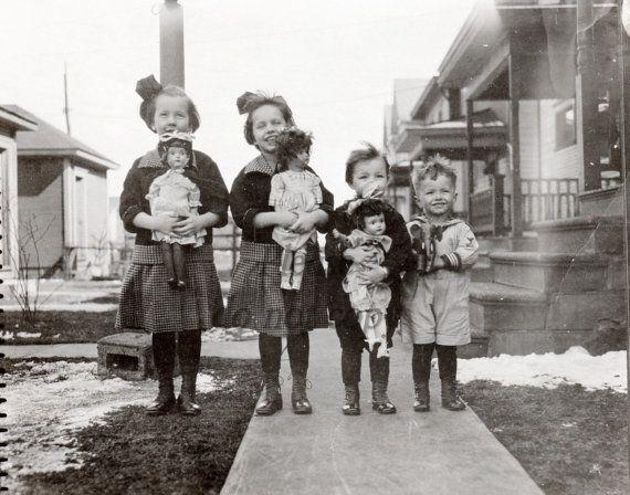 Vintage photo of four children with dolls circa 1920's. Girls with Schoenhut dolls and boy with Schoenhut elephant
