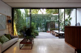 """The main living area is flanked by green spaces, with custom sliding doors made from materials sourced from a metal warehouse. The ceiling is corrugated sheet metal, a """"common and cheap but noble"""" construction material, Teresa says."""