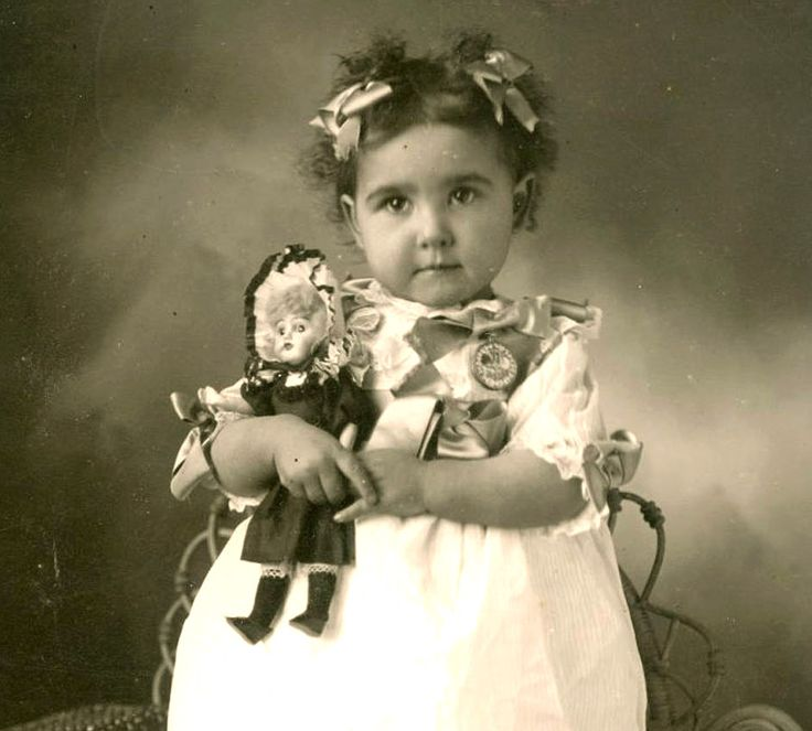 Antique photo of a little girl with her fancy dressed dolly.