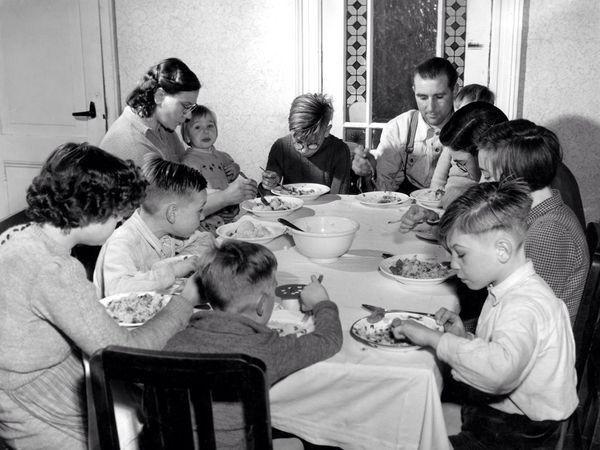 Vader Moeder en 9 kinderen aan het eten.