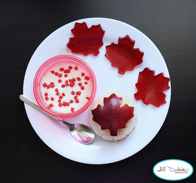 Peanut butter sandwich cut into circle. Maple leaf red apple. Bowl of vanilla yogurt with maple leaf sprinkles. Maple leaf jello jigglers.