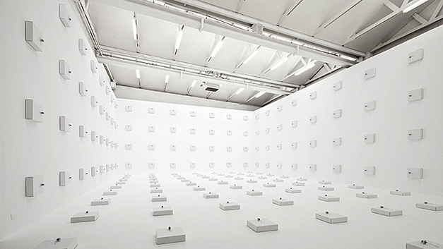 Zimoun - 198 prepared dc-motors, wire isolated, cardboard boxes 30x30x8cm, 2012. Dimensions: 4.75 x 8.5 x 14m / 15.6 x 28 x 46 ft. Size variable. Installation view: CAN, Neuchatel, Switzerland. Curated by CAN Neuchatel. Kindly supported by Pro Helvetia - Swiss Arts Council and Swisslos / Amf für Kultur des Kantons Bern. Sponsoring by Brieger Emballages. Image © Zimoun. Used here by kind permission from the artist. All rights reserved.