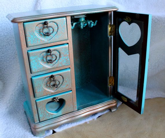 A custom upcycled Jewelry Box in Teal and Copper, wonderfully restored to be a welcome addition to a jewelry connoisseur ... This lovely box is a jewel all on its own! Choose this box and be pleasantly surprised! Give it as a gift to a Bride so she can safely contain all those wonderful gifts she will receive as a wife! Jewelry box stands 12 Inches tall, 10 inches wide and 4 inches deep. It has 4 drawers, a spinning hook for necklaces and a drawer made to cushion rings safely in place.