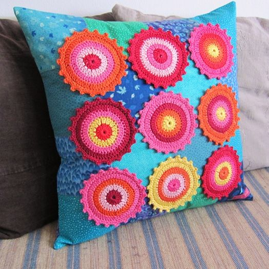 Crochet flower/circle motifs on a fabric covered pillow.  Curious what this would look like in ivory and muted coloured fabric?