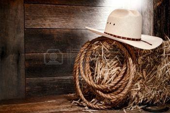 cowboy western: American West cowboy de rodéo chapeau de paille blanc avec corde traditionnelle d'élevage ouest sur une botte de foin dans une grange ranch vieux bois éclairé par une lumière diffuse Banque d