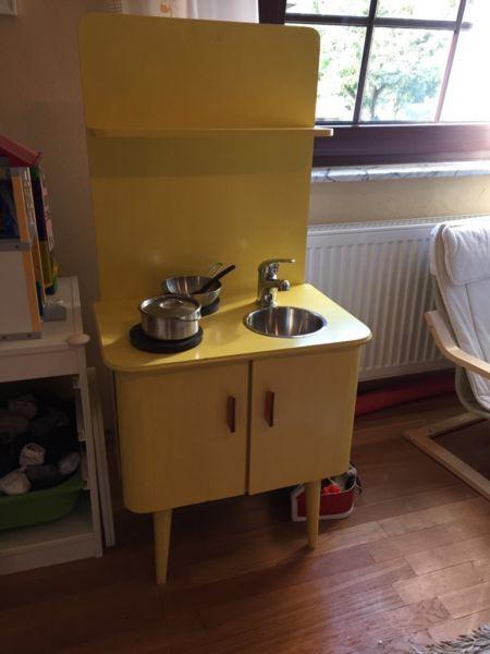 Selbst gebaute Kinderküche nach einem Bastelheft. Basis ein Nachttisch der 60-er Jahre. Möbel umgebaut, per Hand lackiert, Echter Wasserhahn und Spülbecken aus WMF Salatschüssel. Kochplatten sind nur daraufhelegt, viel Stauraum für Geschirr, jedoch ganz kompakte Grösse - für Selbstabholer oder Übergabe FFM Bockenheim.