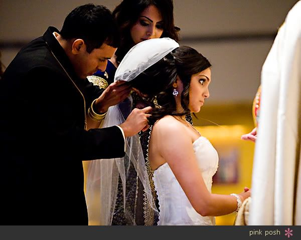 The Indian trend of Christian Wedding.  In the Indian Christian Weddings, it is the traditional way where the groom places the Mangalsutra or so called 'Thali' around the bride's neck instead of giving her a ring.