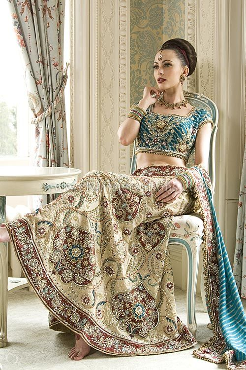 Modern bridal lehenga with a teal lined blouse and a champagne gold skirt with maroon patchwork