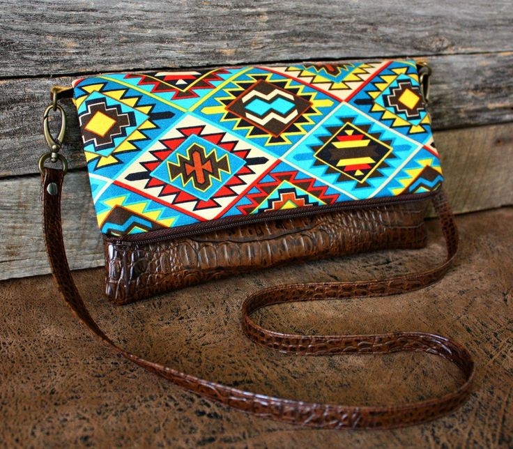 Made to order. Ships out 2 to 4 days after purchase.    This foldover clutch has an eye-catching Navajo Southwestern fabric with a brown faux leather for the bottom and strap.    This is the perfect size to carry your items in: your cell phone, keys, make-up, money, small camera, wallet, and room for your kindle.  Dont want to carry a big bulky purse? This is the perfect size to grab and go for a day out shopping!    Measurements:  When flat: 11 tall by 10 1/2 wide When folded: Approxima...