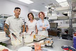 Portrait confident pastry chefs in commercial kitchen