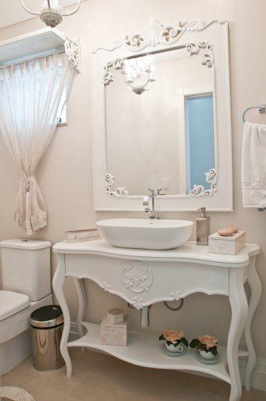 Já o lavabo exibe estilo provençal, com mobiliário na cor branca. A bancada da pia foi formada por um aparador e cuba oval. Sobre a janela, uma prateleira garante um delicado acabamento com a cortina.
