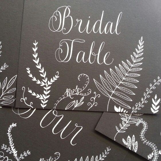 Table numbers/names in white calligraphy on black card with botanical fern inspired drawings and Bride & Groom initials #floralovely #calligraphy #moderncalligraphy #handlettering #wedding #weddingcalligraphy #weddingcalligrapher #australiancalligrapher #love