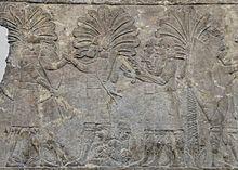 Bas-relief néo-assyrien représentant un scribe écrivant en assyrien cunéiforme sur une tablette d'argile et un autre écrivant en araméen alphabétique sur un papyrus ou parchemin.