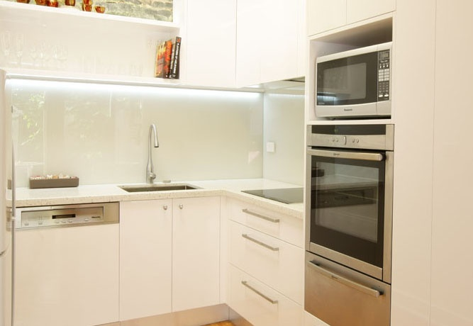 Caesarstone and backlit glass splash-backs in a contemporary kitchen renovation - Carlton, Melbourne.