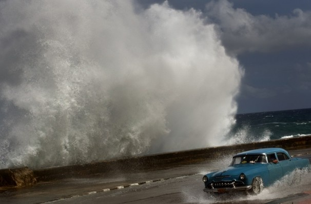 A driver maneuvers his car along a wet road as a wave crashes against the Malecon in Havana. Hurricane Sandy blasted across eastern Cuba