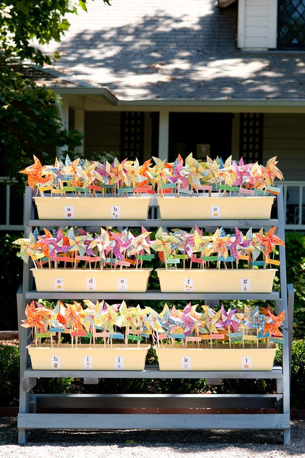 The pinwheels became the escort cards for the wedding –a paper strip attached to the dowel had each guest's name and table number hand-written