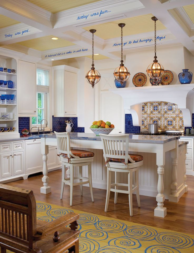 Playful sayings by friends scrawl along the white-wood beams in this nearly all-white kitchen. Blue mosaic-glass tiles, Blue Macauba granite countertops and dangling globe-wrapped copper pendants add color.