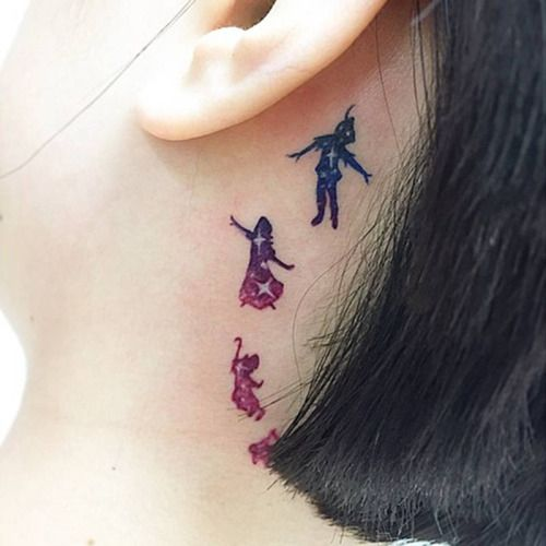 Watercolor/Galaxy style Peter Pan inspired tattoo behind the...