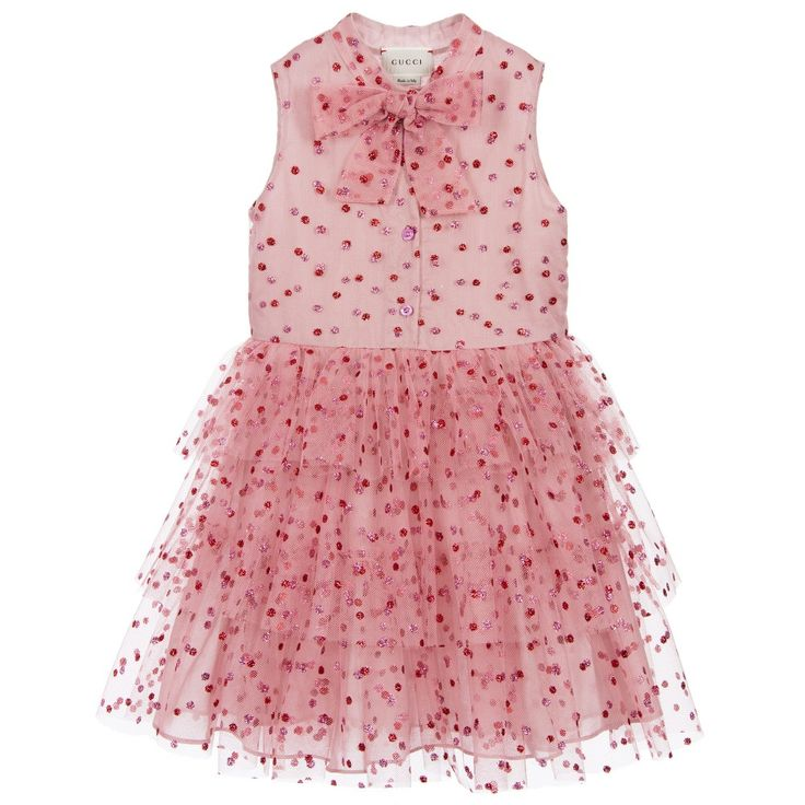 Girls gorgeous pink tulle dress by Gucci, covered in contrasting bright pink and red glittery spots. An appliqué bow covers the popper at the neck, and there is a logo button fastener down the front. The dress is fully lined in soft cotton and has tiers of tulle on the skirt, with a concealed side zip fastener.