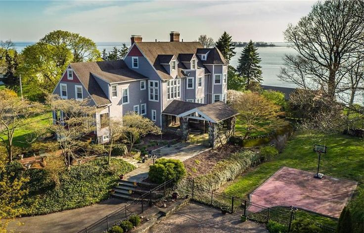 """Quite the contrary — the 6,251-square-foot house, built in 1890, has been updated with a bevy of contemporary amenities, including a full bar on its third floor, a modern gourmet kitchen and an all-weather enclosed porch.  The rear used to face Gulf Street and Welch's Point Road, back when the house was part of a larger estate, owned by the Pond family said homeowner Paul Staneski.  """"Carriages used to let people out here when they came to the house,"""" Staneski said, pointing to what it is now…"""