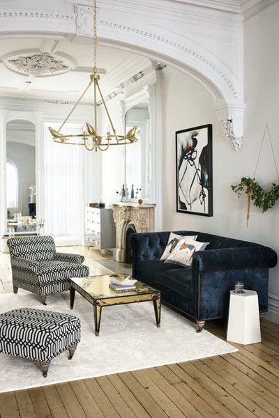 Living space with detailed architecture, wood floors, and a blue velvet sofa