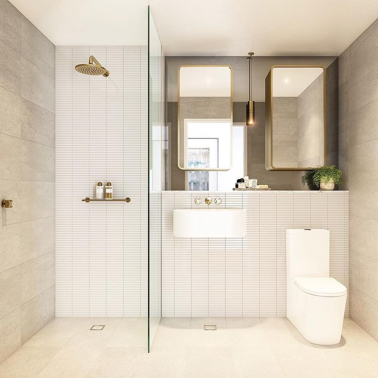 Bathroom: open walk-in shower, single fixed frameless shower screen panel, brushed gold/brass shower head, brushed gold/brass wall taps, his-and-hers brushed gold/brass rounded-corner mirror cabinets, mirror splashback, wall-mounted basin, back-to-wall toilet, brushed gold/brass pendant light, pale stone-look tiles