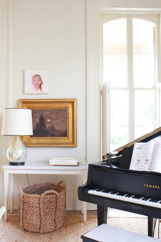 Simple white console with large basket underneath, statement lamp, vintage art in gold frame and modern portrait: