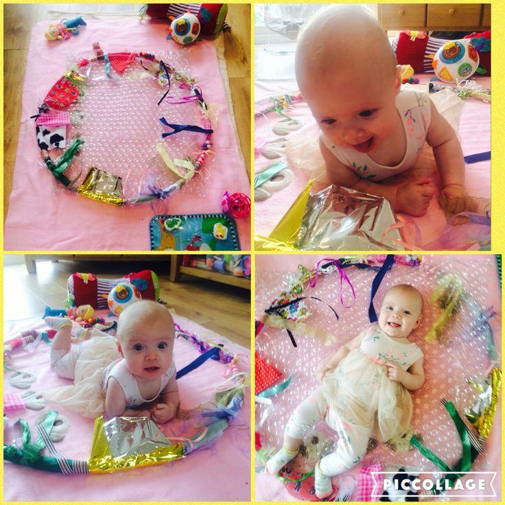 Hulahoopreifen mit verschiedenen Bändern, damit Baby die unterschiedlichen Texturen kennen lernen kann. Vielleicht liegt bei uns noch ein alter Reifen herum.