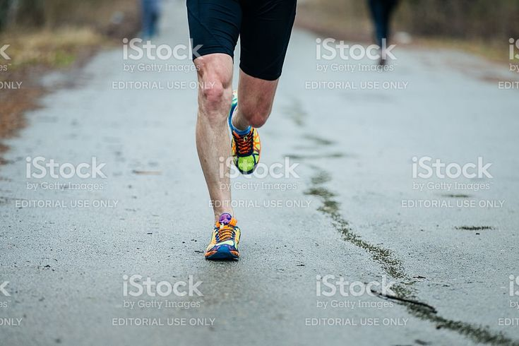 Chelyabinsk, Russia - April 23, 2016: closeup feet of young runner men running along road in Park during Half marathon in woods