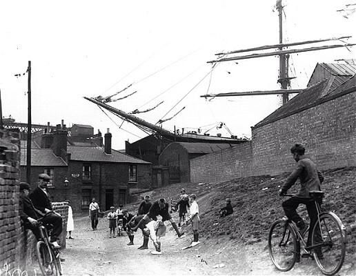 Playing leap frog under the bowsprit of the schooner 'Penang' in Millwall Dock, London c.1932.