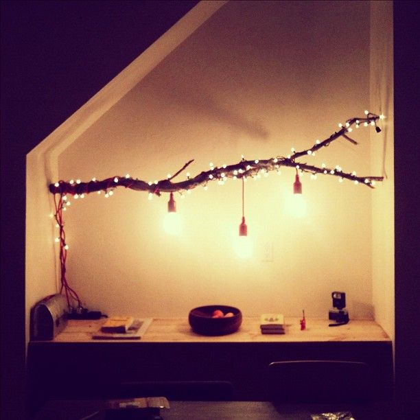 not just a stick. A cute masculine decor piece made that little bit more feminine by the fairy lights and hanging lamps...