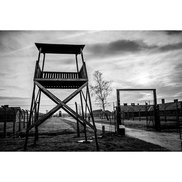 Auschwitz II-Birkenau. The gate leading to the road between sectors BIa and BIb. The building on the left and right in the foreground are two disinfection stations where prisoners were registered and washed. --- Photo by @javier_palacios_prieto --- #Auschwitz #Birkenau #AuschwitzMemorial #history #bw #architecture #watchtower #concentrationcamp