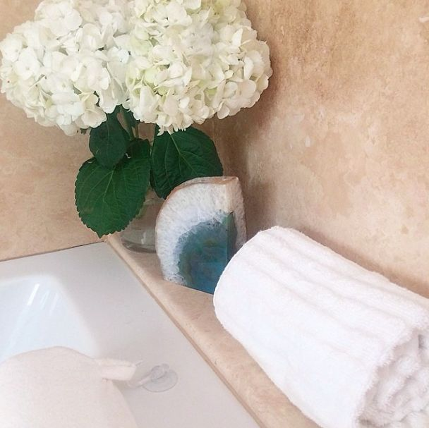 crystal geode and fresh flowers on the edge of a tub.   www.RachelTalbott.com