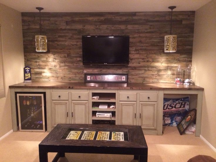 I reused old kitchen cabinets to add storage for our game room. Did butcher block on top. We did a reclaimed wood wall, added license plate wall sconces, found a shadow coffee table and added licenses plates to tie it all together!