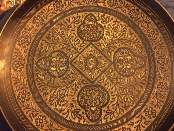 A beautiful Damascene-style plate with a flower and leaf pattern.  The etched brass plate is approximately 9.75 in diameter and has a wire on the backside to hang on the wall.  Very good condition, though a bit of black is worn, see the 9:00 position on the first photo.  Please take