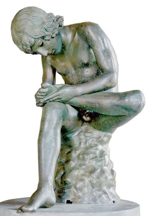 """CHŁOPIEC WYCIĄGAJĄCY CIERŃ  Chłopiec wyciągający cierń to popularny motyw rzeźby antycznej. Jedna z jego wersji - marmurowa kopia rzeźby z III w. pne znajduje się w British Museum w Londynie, ale najsłynniejsza jest wykonana z brązu wersja eksponowana w Pałacu Konserwatorskim w Rzymie i nazywana """"kapitolińską"""". O oryginałach wiadomo niewiele (a raczej nic)."""