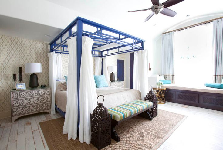 Blue Mediterranean canopy bed with white bedsheets