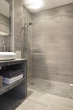 Love the larger tiles on the walls of the shower and the floor of the shower... Love the transition into the rest if the room but would want an actual glass door, and a warmer color palette than grey