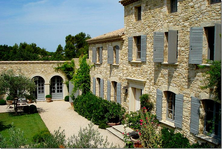 Arched French doors. Blue shutters. Pea gravel terrace.