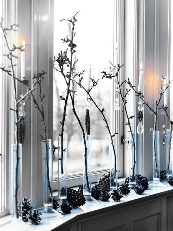 Веточки украшенные хрусталем, шишки и свечки создают праздничную атмосферу на этом окне. .